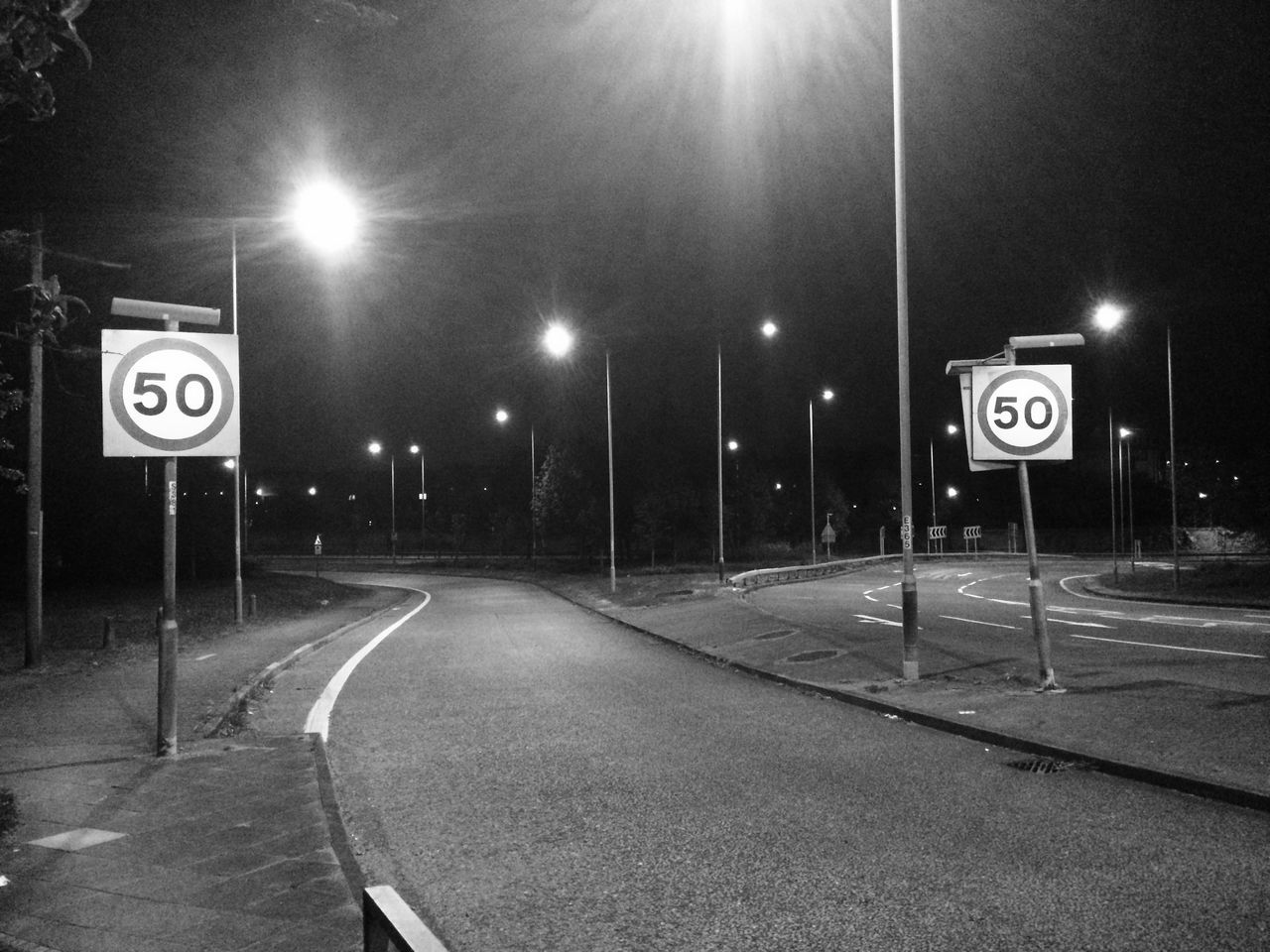 Black and White Picture of 50 Miles Per Hour Speed Limit Sign. Communication Empty Road Guidance Illuminated Information Sign Night Number Outdoors Road Road Sign Speed Limit Sign Street The Way Forward Traffic Arrow Sign Transportation