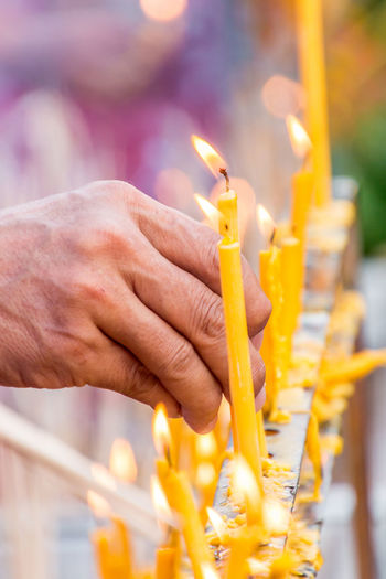 People are lighting candle to pray for goodness Light Buddhism; Burning Candle; Close-up Culture; Day Fire Flame Focus On Foreground Goodness; Heat - Temperature Holding Human Hand Men Merit; One Person Outdoors People Pray; Real People Religion Spirituality Tradition; Worship;