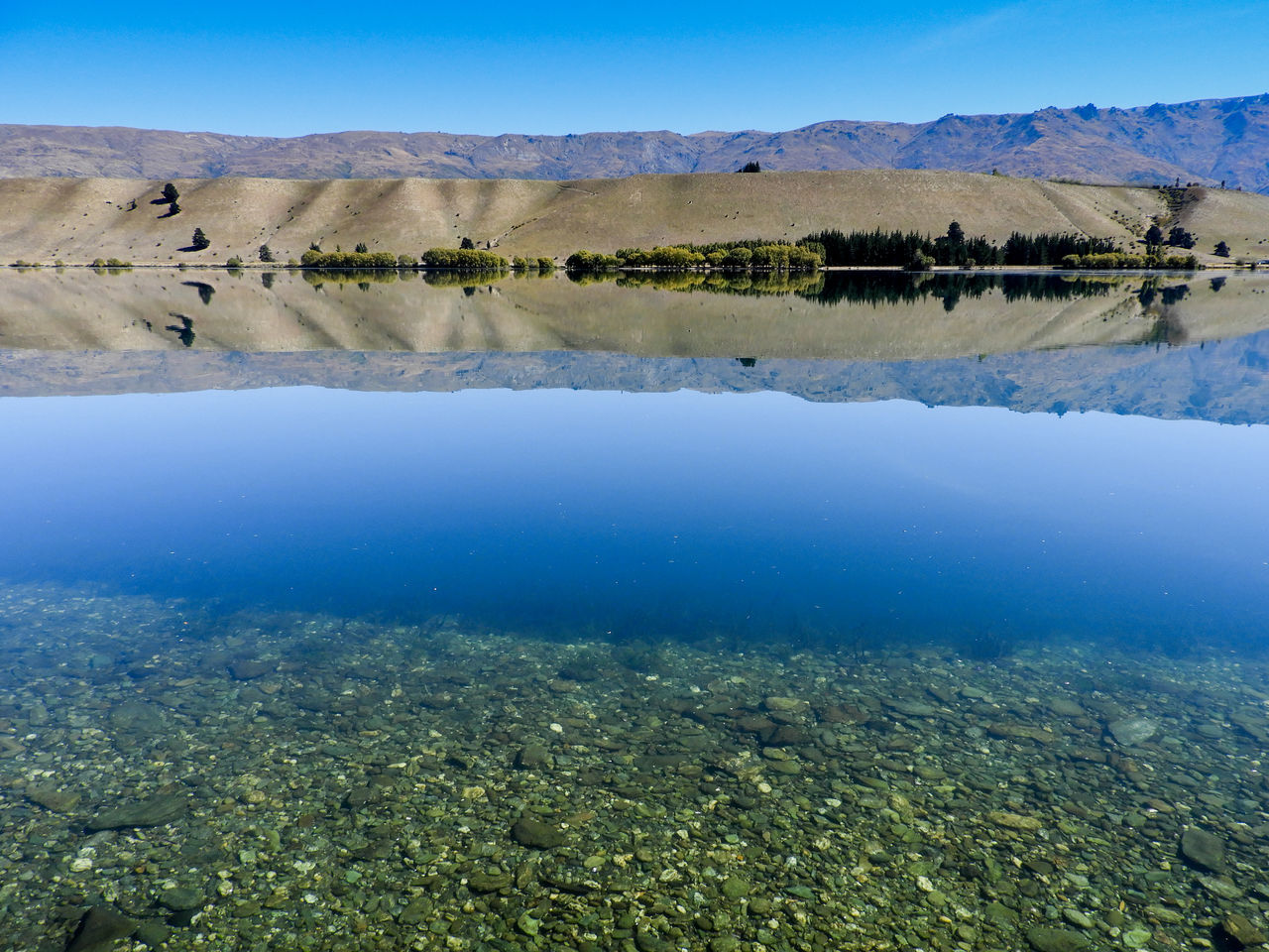 A fetching still lake scene, taken as I felt captured by the calmness of the water. Beauty In Nature Blue Clear Sky Day Hills Lake Landscape Nature No People Outdoors Pebbles Reflection Reflection Scenics Sky Tree Water