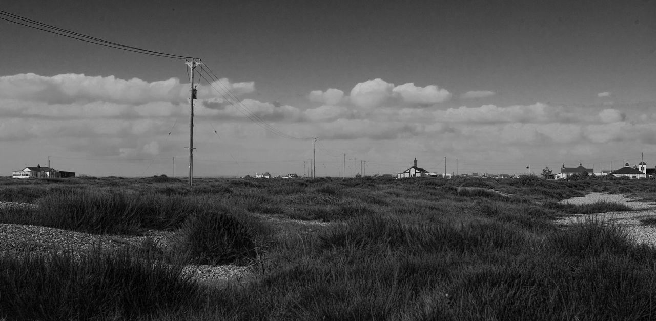Telephone Pole On Grassy Field Against Sky