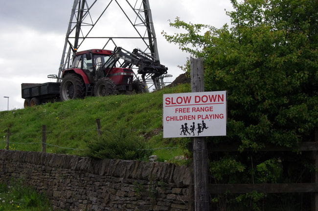 Sign Caution Children Playing Free Range Tractor Red Tractor Walking Around Wardle Greater Manchester England Electricity Pylon Stone Wall Green Grass Trailer Bush