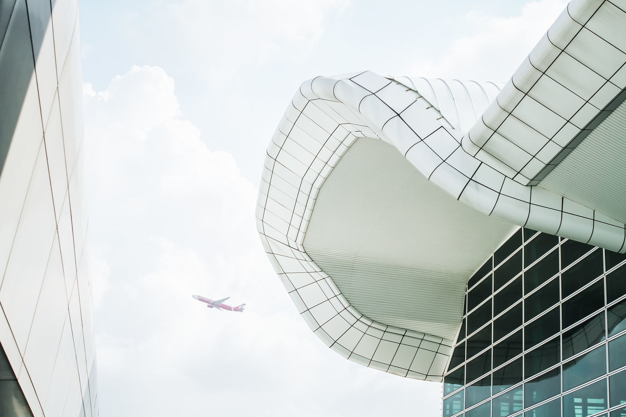 sky, day, architecture, low angle view, built structure, cloud - sky, modern, no people, outdoors, airplane, building exterior, flying