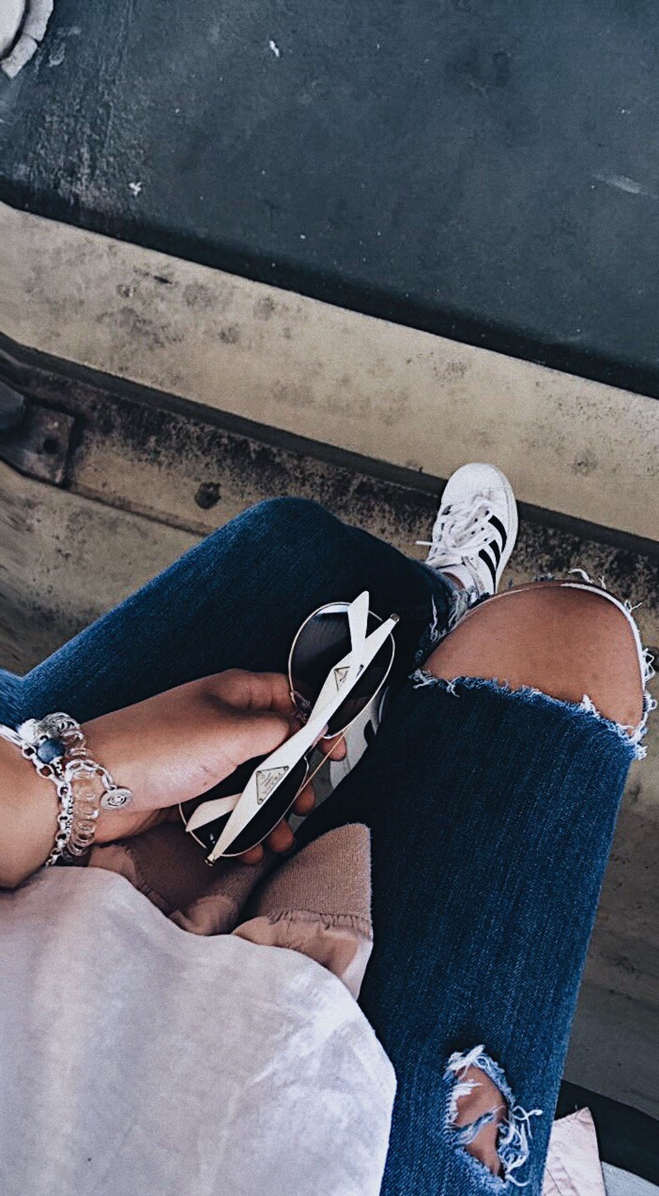 jeans, human leg, high angle view, low section, one person, skateboard, casual clothing, real people, leisure activity, shoe, lifestyles, day, sitting, human body part, outdoors, men, close-up, human hand, adult, people