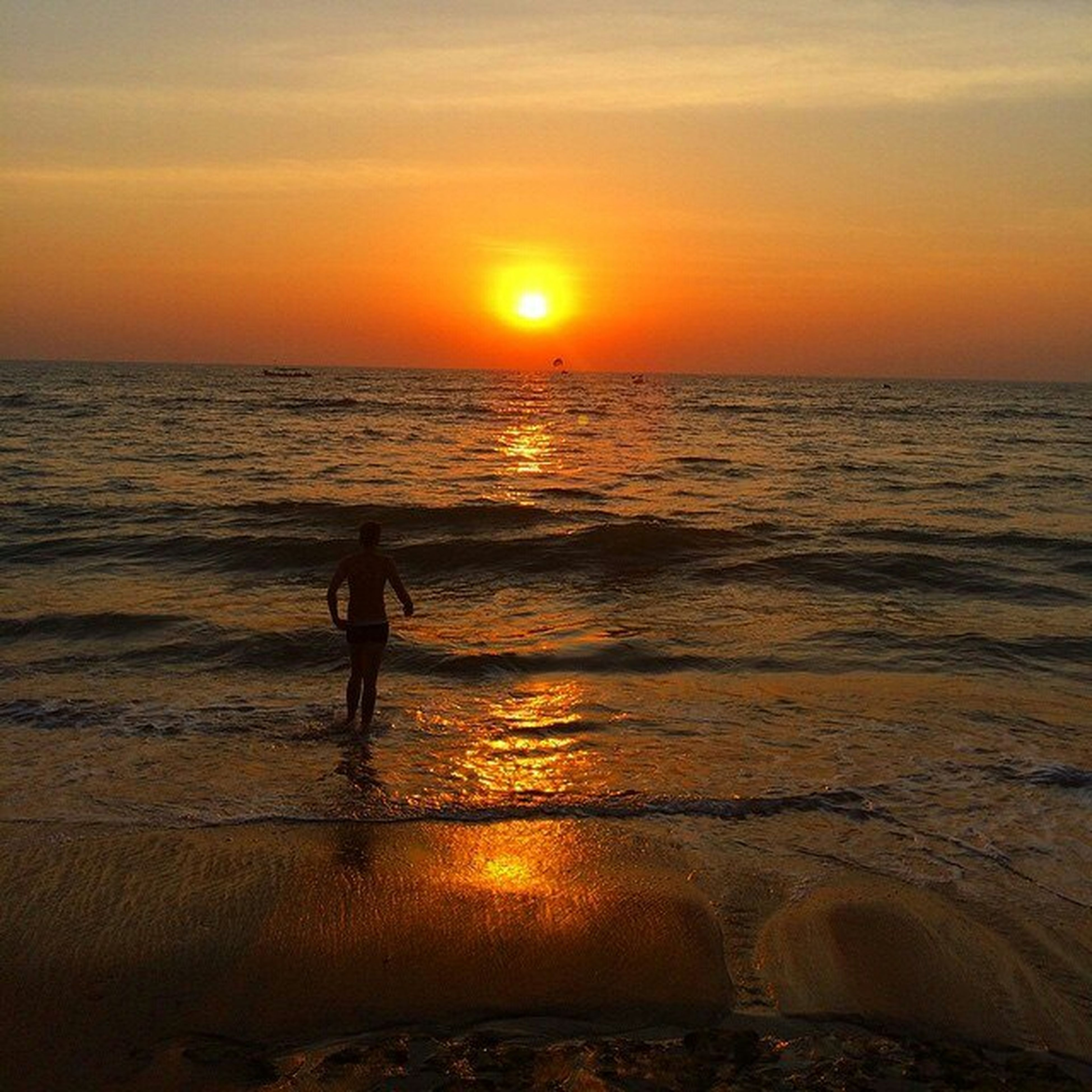 sunset, sea, water, beach, horizon over water, silhouette, leisure activity, orange color, shore, lifestyles, scenics, sun, beauty in nature, full length, wave, vacations, standing, tranquil scene