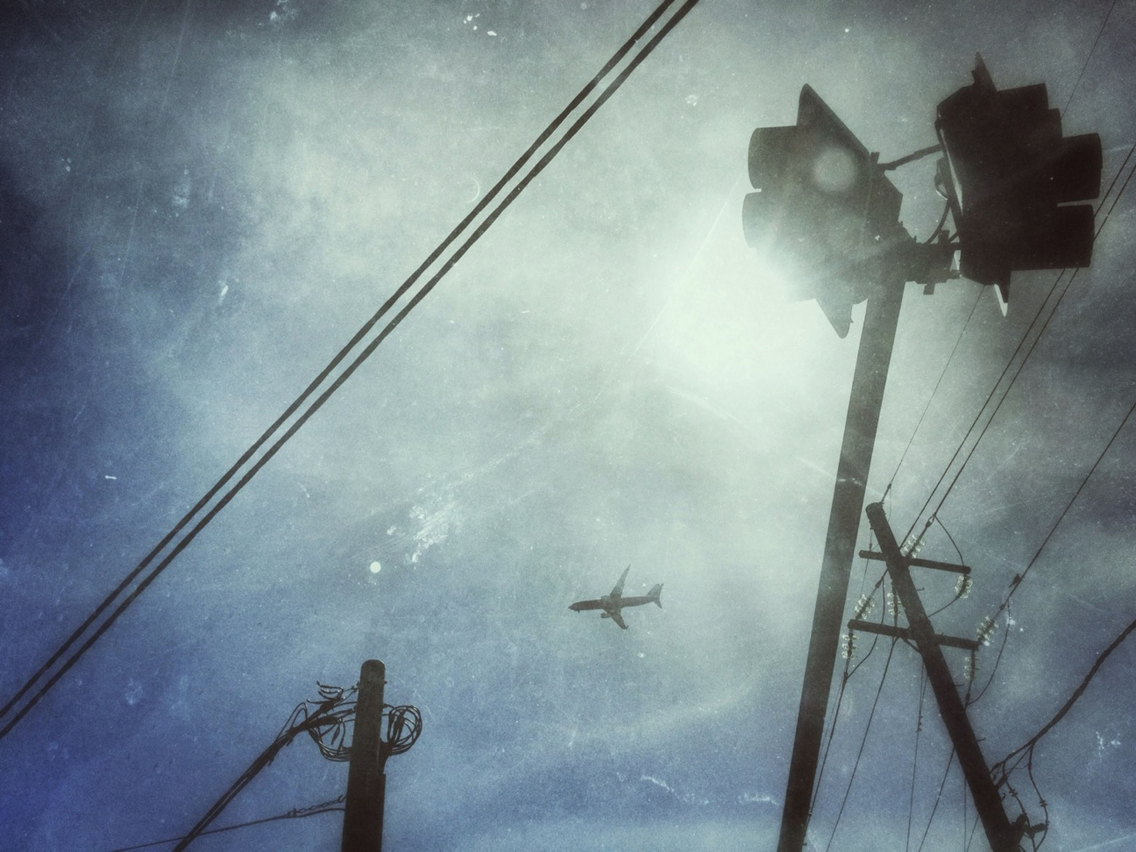 low angle view, sky, cloud - sky, transportation, cloudy, mode of transport, flying, street light, airplane, connection, cloud, day, power line, no people, nature, outdoors, sunlight, silhouette, weather, air vehicle