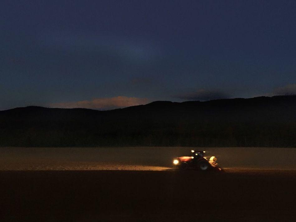 Farming in Maine at sunset by tractor lights. Sky Tractor Red Tractor Farming Farm Vehicles Agriculture Night Tractor Lights Mountain Silhouette Landscape Dark Outdoors Illuminated No People Headlight
