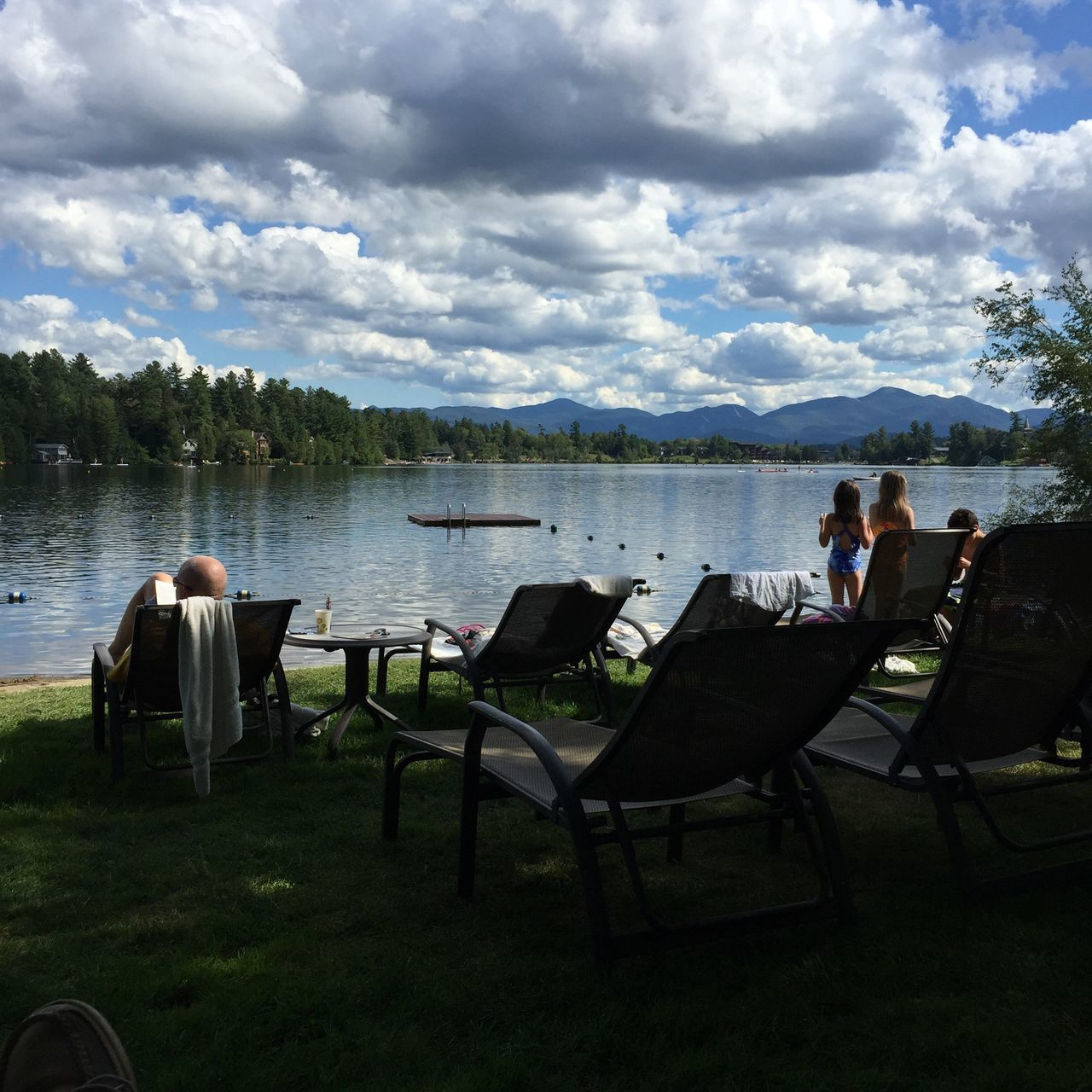 Sky And Clouds Adirondack Mountains Lake Placid Mirror Lake Mountain View Water Nature Beauty In Nature Lake Chair Sky Real People Men Leisure Activity Standing Full Length Grass Sitting Scenics Outdoors Cloud - Sky Rear View Day Young Adult Tree