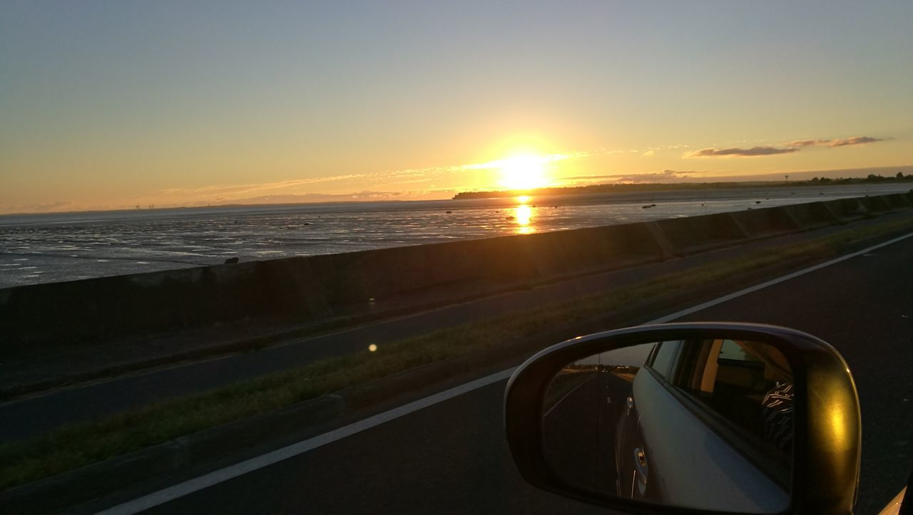 sunset, transportation, side-view mirror, mode of transport, car, reflection, sea, sky, land vehicle, sun, nature, journey, scenics, beauty in nature, water, road, road trip, vehicle mirror, no people, outdoors, horizon over water, close-up, day