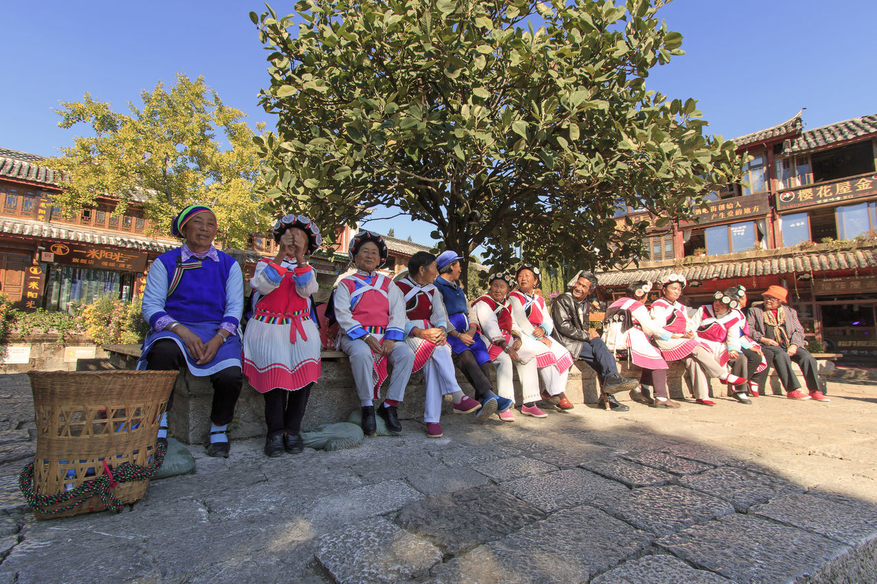 Lijiang, China - November 10, 2016: Old women dressed with the traditional attire of their minority in Lijiang Old Town Adult Adults Only ASIA Bai Celebration China Dali Yunnan Day Lijiang Men Minority Mosuo Musical Instrument Naxi Outdoors People Performance Shangri-La Teamwork Tree Yunnan