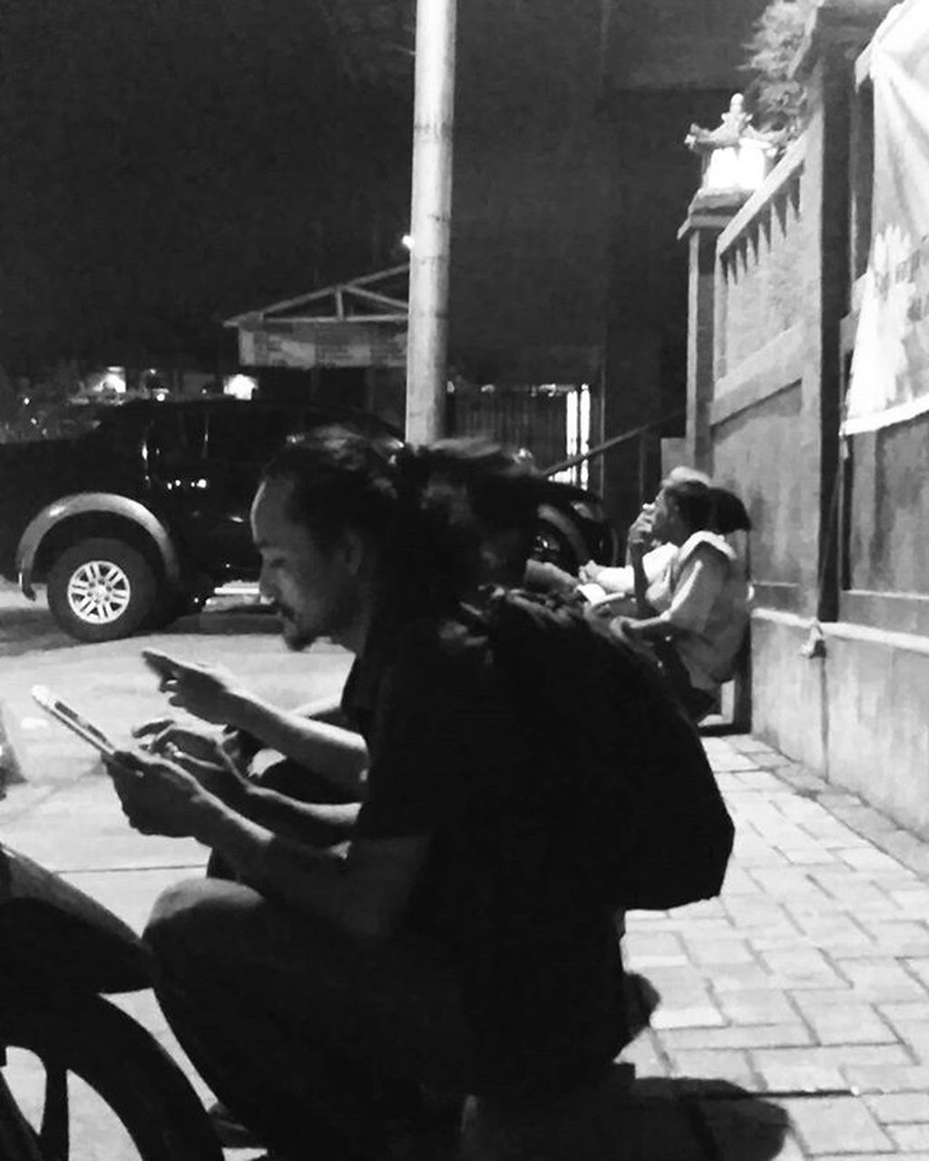 street, communication, sitting, holding, mobile phone, wireless technology, outdoors, real people, one person, bad habit, night, city, technology, one man only, adult, people, only men, adults only, young adult