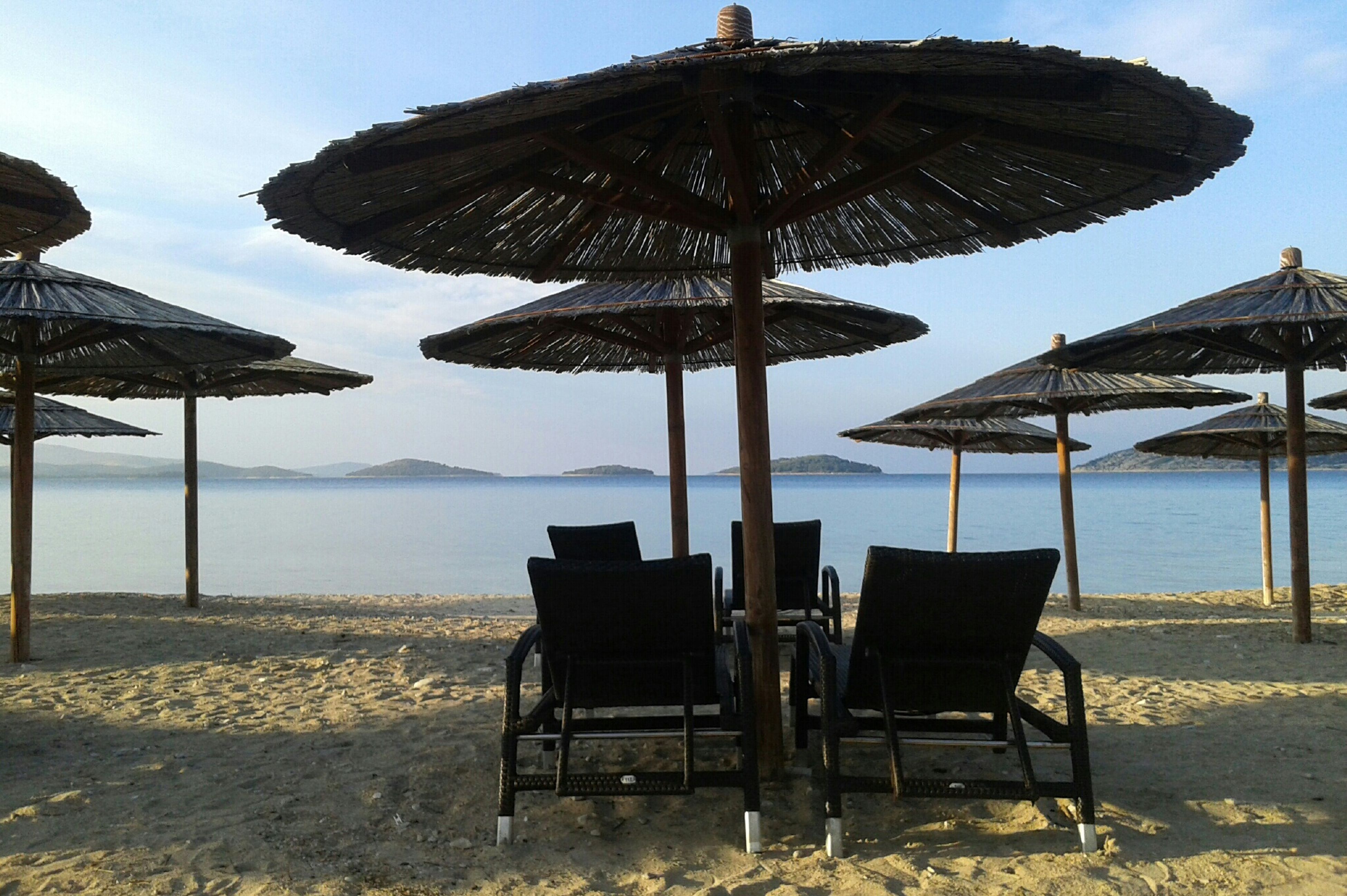 sea, beach, water, chair, tranquility, horizon over water, tranquil scene, bench, absence, sky, sand, empty, scenics, relaxation, shore, vacations, nature, thatched roof, beach umbrella, parasol
