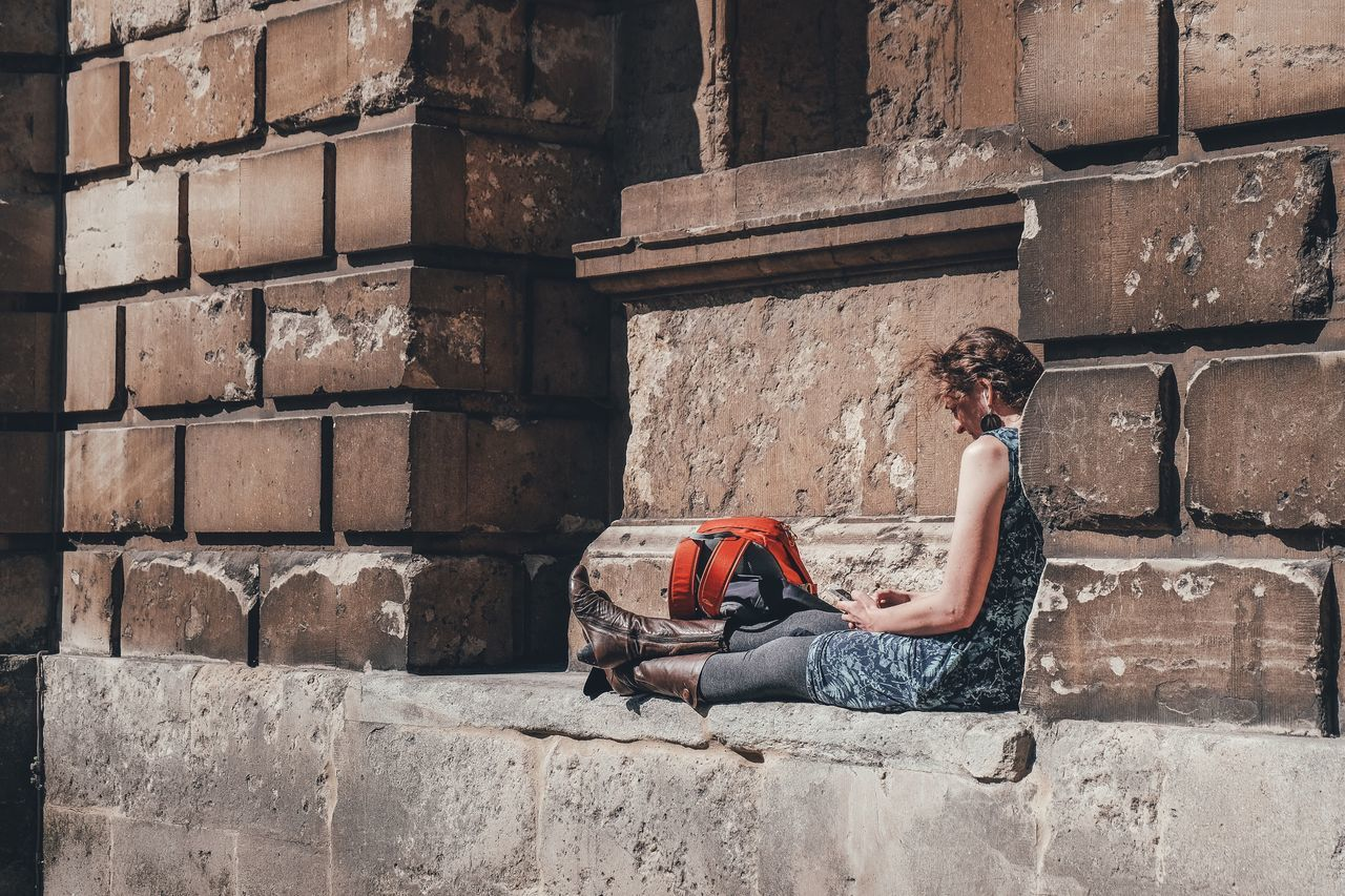 The Street Photographer - 2017 EyeEm Awards Building Exterior Girl Brick Wall One Person Sitting Architecture Young Women Reading Books Full Length Retaining Wall Sitting Outside Portrait