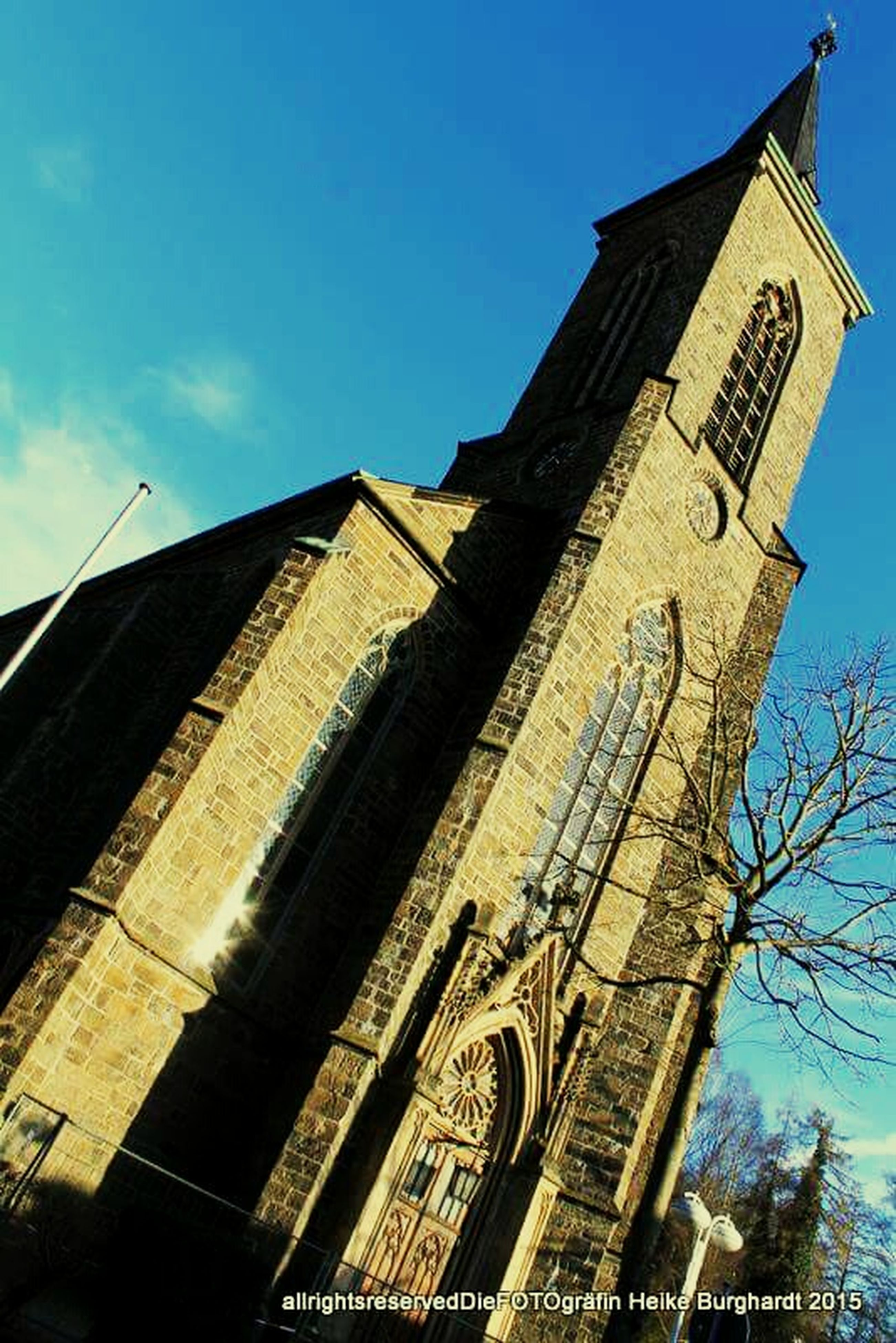 architecture, building exterior, built structure, low angle view, church, religion, place of worship, spirituality, tower, sky, history, clock tower, cathedral, blue, clear sky, old, cross, tall - high