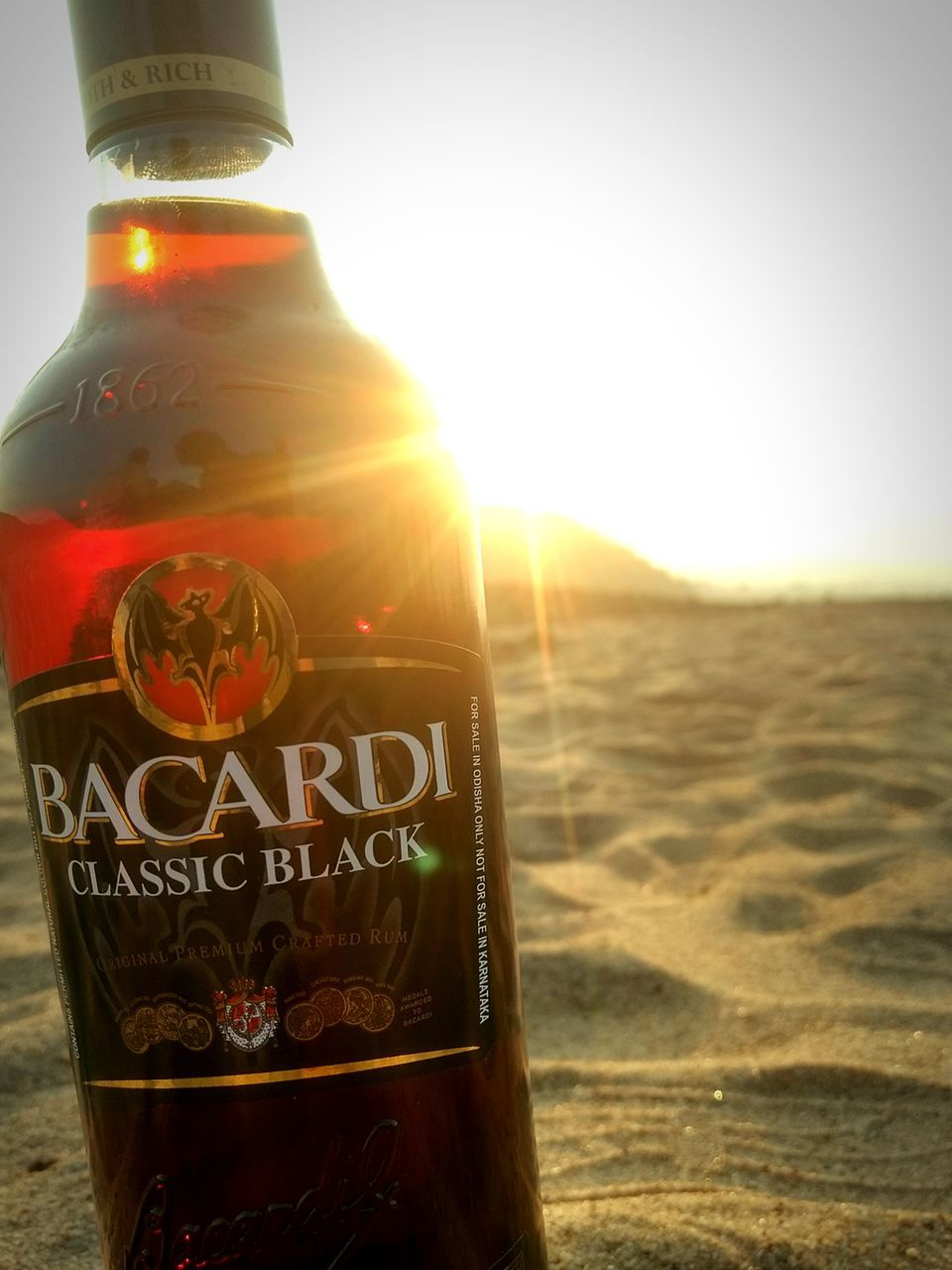 bottle, text, drink, beach, alcohol, sand, sunlight, sun, outdoors, close-up, no people, vacations, day, nature, water, beauty in nature, freshness, sky