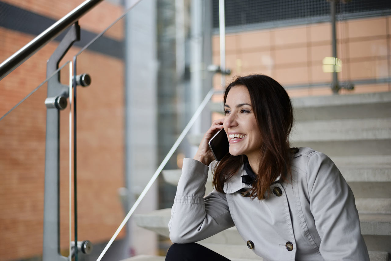 businesswoman with smartphone Business Businesswoman Cellphone City Communication Confidence  Connect Happy Hearing Laughing Listening Livestyle Manager Mobile Optimistic Phone Smartphone Speaking Successful Technology Telephone Urban Woman