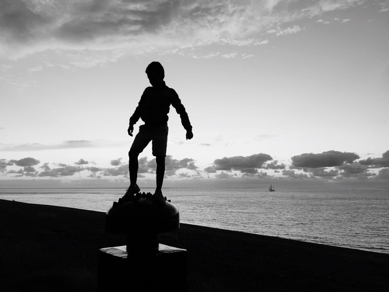 Silhouette Of Boy At Beach Against Sky
