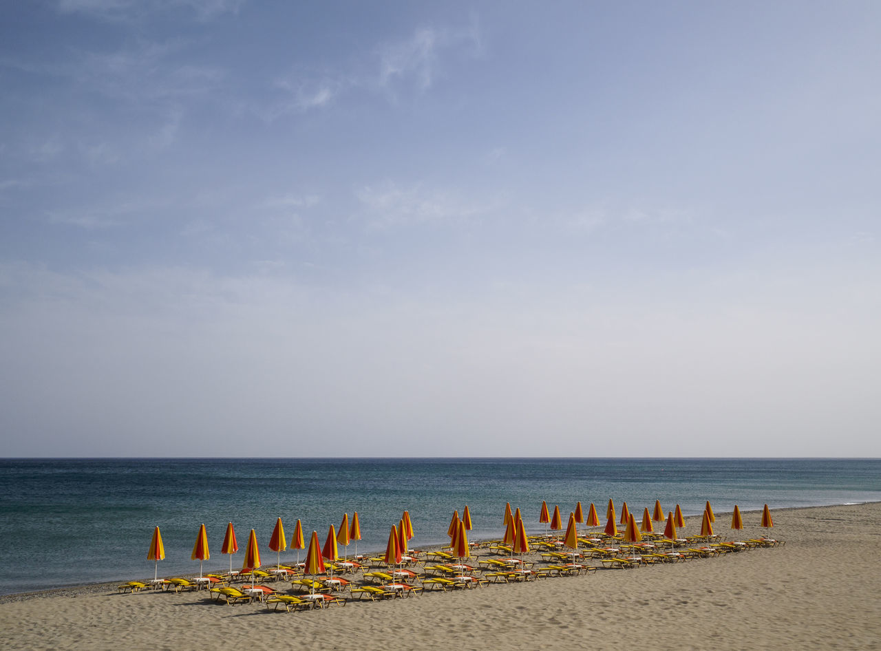beach at Rethymno Crete with the umbrellas and loungers set out for the day Beach Beach Umbrella In A Row Outdoors Protection Sand Sea Sky Sun Lounger Umbrella Vacations