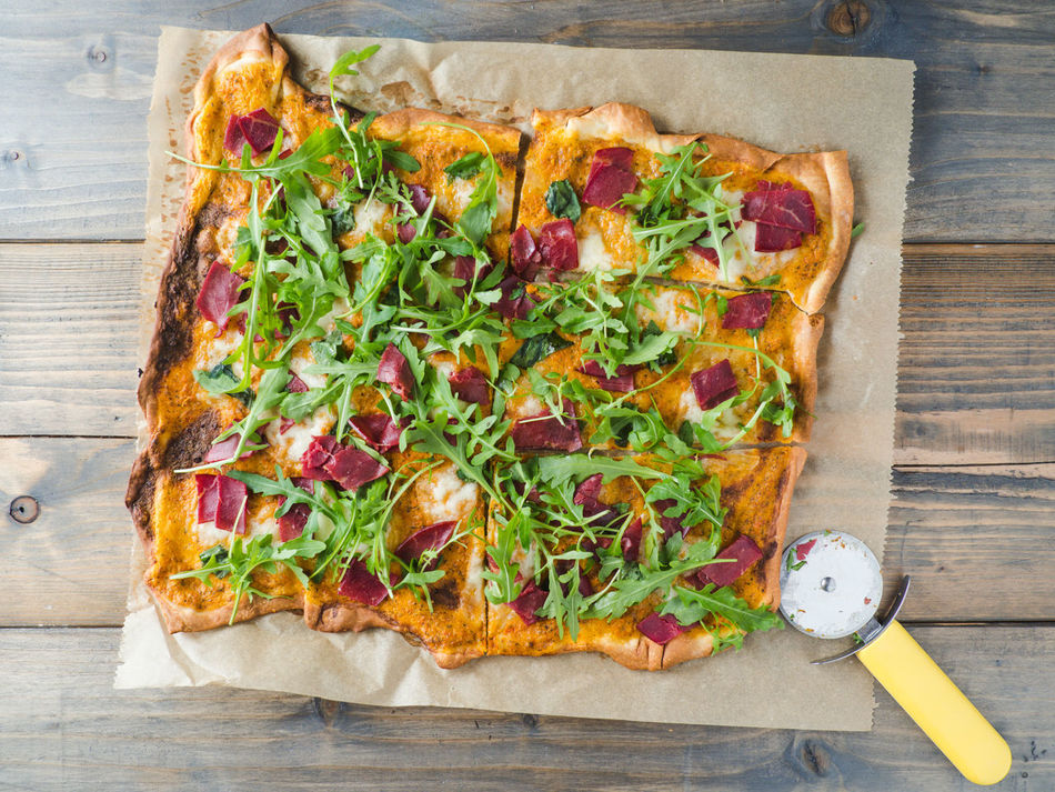 Sliced appetizing pizza with smoked meat and arugula on a wooden background Arugula Baked Cheese Cooking At Home Delicious Dinner Dinner Time Fastfood Food Ham High Angle View Italien Italien Food Meal Meat Overheade Pizza Pizza Cutter Rustic Style Sliced Smoked Snack Tasty Tradional Wooden Background