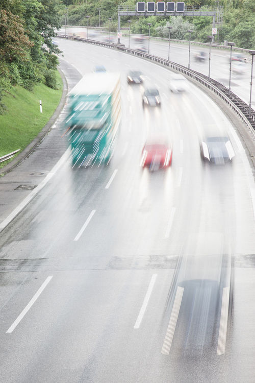 Cars speeding on German highway Autobahn in Berlin in wet weather conditions with road moist from rain. Asphalt Busy Cars Commuting Driving Rain Road Rush Hour Speeding Traffic Traveling Weather Autobahn Conditions Day Highway Motion Motorway No People Outdoors Road Safety Transportation Water Wet