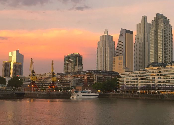 Buildings Cityscape Orange Sunset Dawn Clouds And Sky Yacht Madero Harbor Puerto Madero Skyline Architecture Skyscraper Building Exterior Built Structure City Waterfront Cityscape Urban Skyline Modern Water Sky River No People Travel Destinations Cloud - Sky Outdoors Nautical Vessel Day