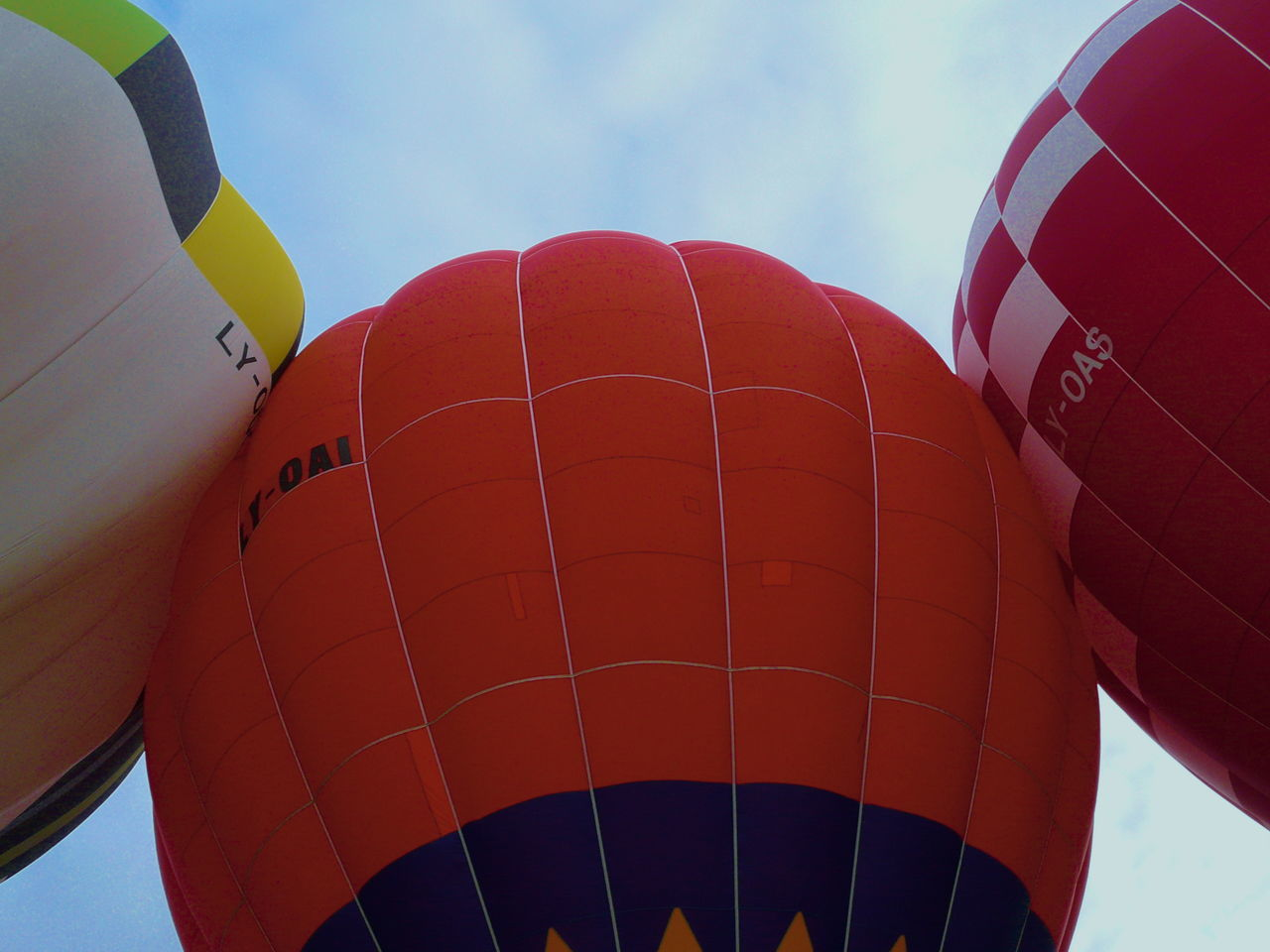 hot air balloon, transportation, sky, traditional festival, low angle view, air vehicle, celebration, outdoors, adventure, mode of transport, ballooning festival, day, mid-air, red, flying, no people, close-up