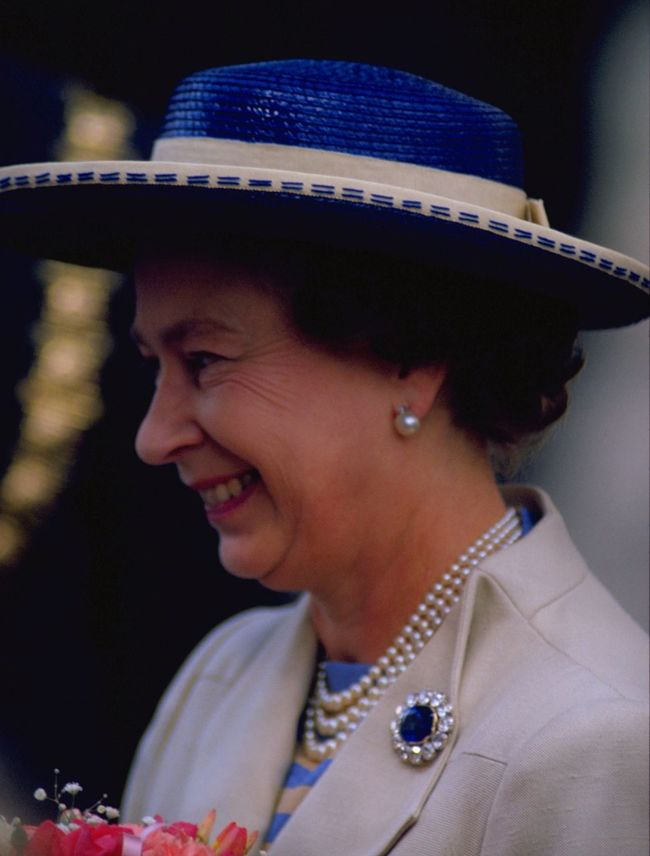 The Queen is Head of State of the United Kingdom and 15 other Commonwealth realms. The first child of King George VI and Queen Elizabeth, she was born on 21st April, 1926 and became Queen at the age of 25. The Coronation of Queen Elizabeth II took place in Westminster Abbey on 2nd June, 1953; over a year after her father's death. Blue Hat British Commonwealth Diamond Brooch Focus Object Flowers Grandmother Head Of State Headshot Her Majesty Human Face London London LifestyleMonarchy Pearl Necklace  Pearls People Portrait Queen Elizabeth  Queen Elizabeth II Royal Photography Royalty Smiling The Queen People And Places