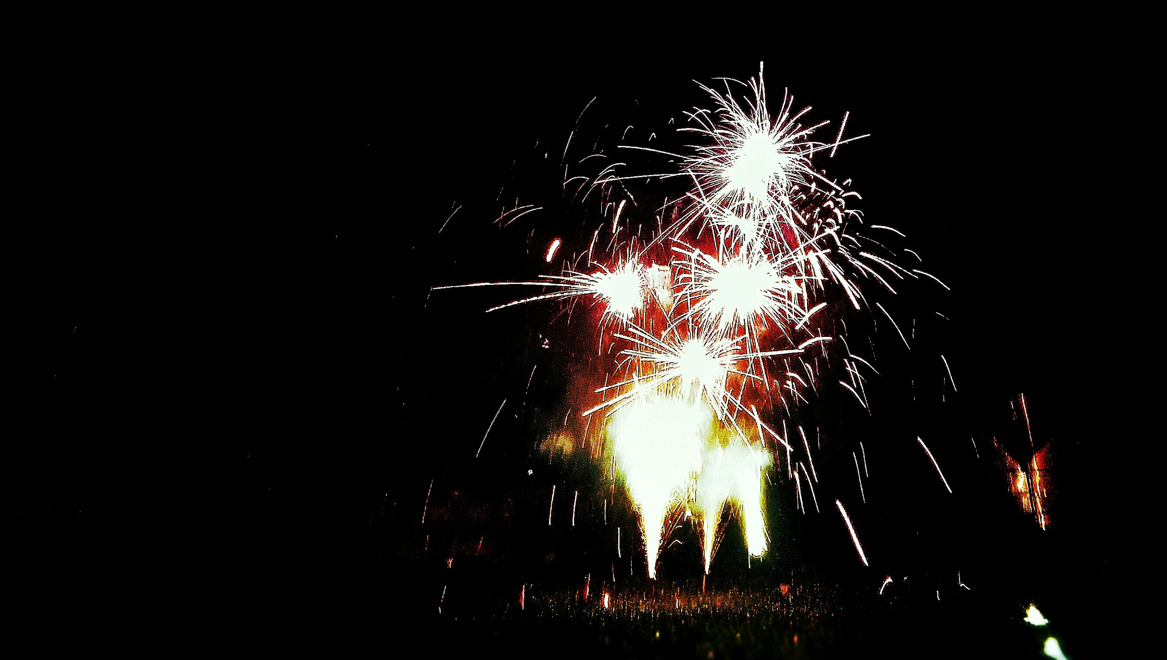 night, firework display, long exposure, exploding, illuminated, firework - man made object, motion, sparks, celebration, glowing, fire - natural phenomenon, firework, arts culture and entertainment, blurred motion, event, entertainment, burning, low angle view, sky, sparkler