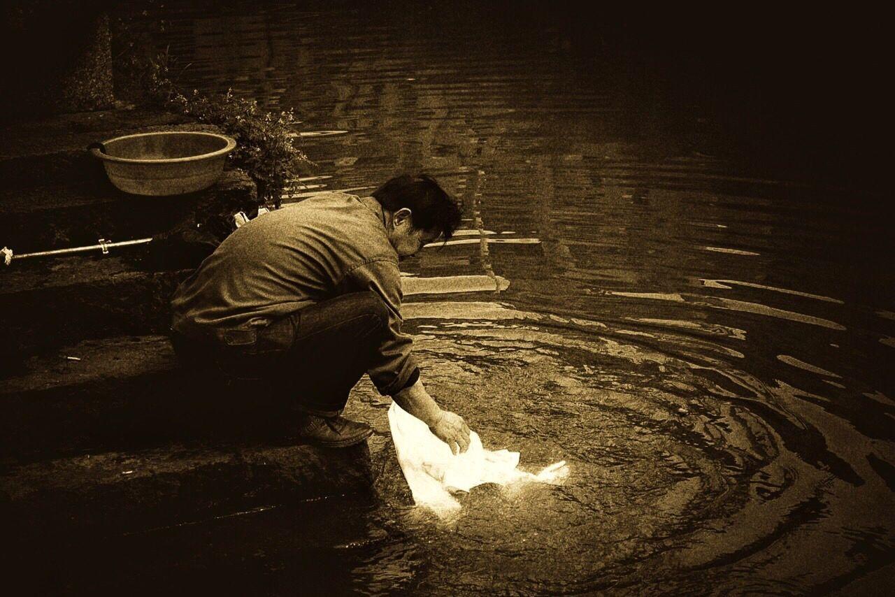 High Angle View Of Man Washing Cloth In Lake