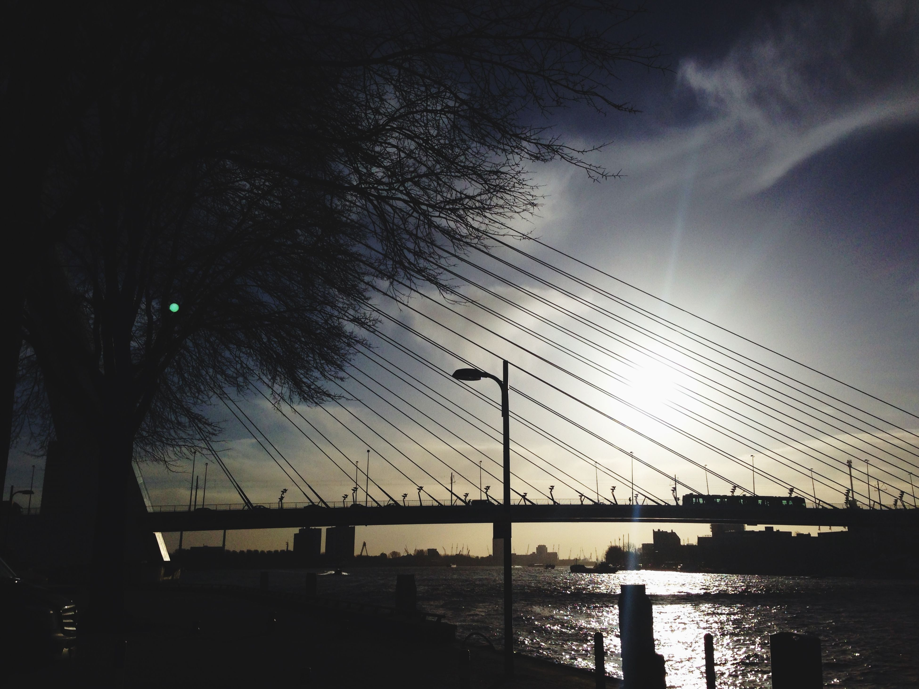 connection, water, bridge - man made structure, built structure, architecture, sky, silhouette, river, sunset, bridge, engineering, transportation, cloud - sky, waterfront, suspension bridge, dusk, city, nature, reflection, outdoors