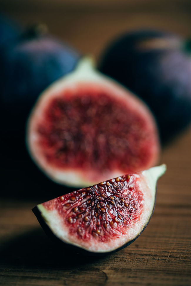 Fresh fig, sliced and quartered Agriculture Biology Close-up Cross Section Fig Food And Drink Freshness Fruit Grapefruit Halved Healthy Eating Juicy No People Red Seed SLICE Vertical