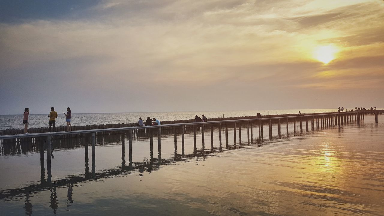 water, sea, beach, sky, horizon over water, sunset, nature, scenics, beauty in nature, tranquil scene, leisure activity, tranquility, outdoors, cloud - sky, weekend activities, real people, sand, men, large group of people, lifestyles, vacations, standing, day, people