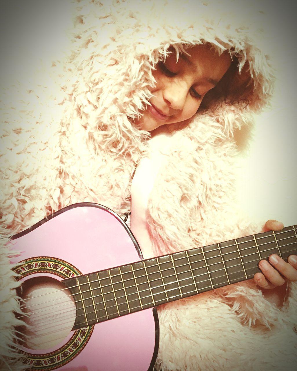 Girl Playing Guitar While Wearing Fur Jacket