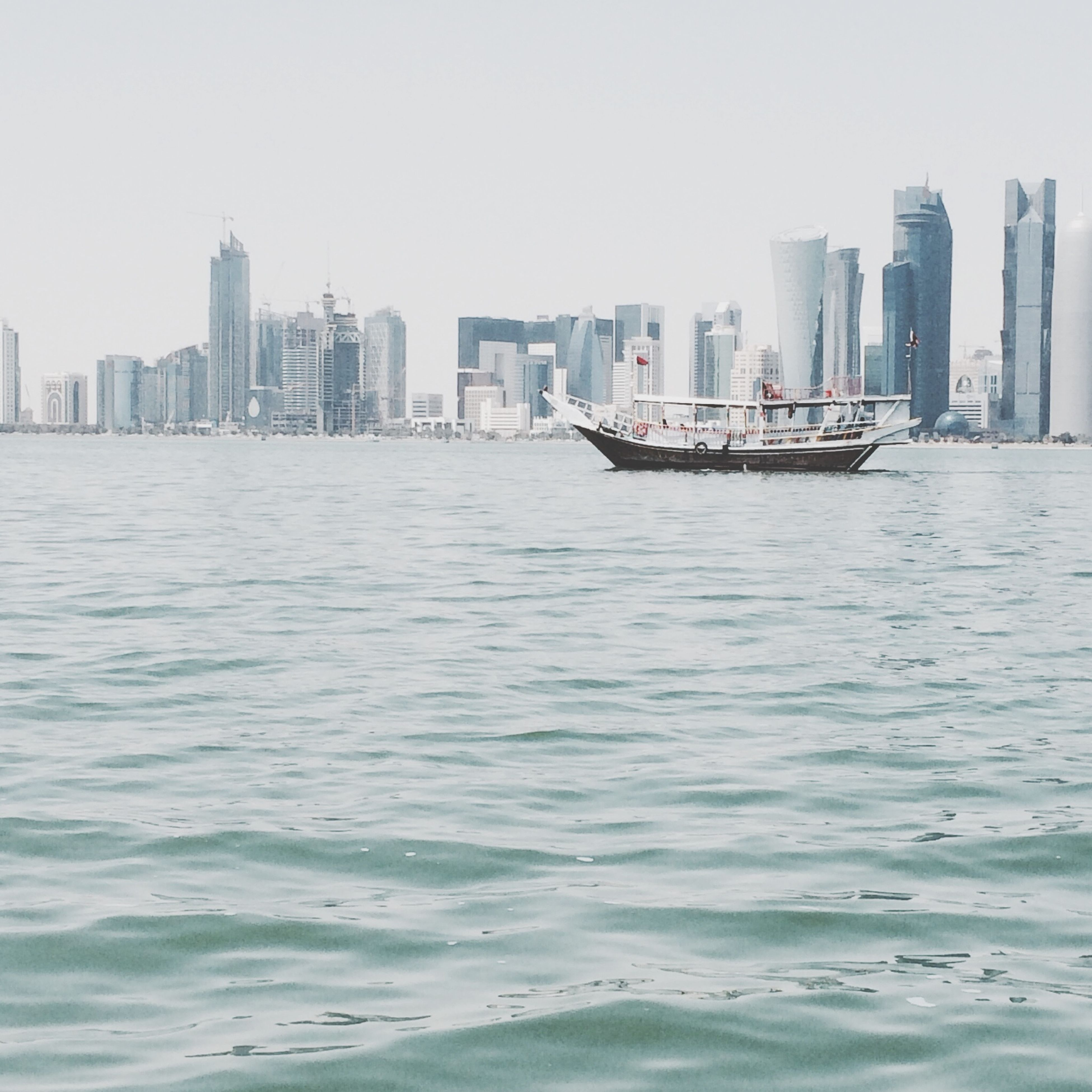 building exterior, city, architecture, skyscraper, water, built structure, waterfront, clear sky, urban skyline, tall - high, modern, cityscape, sea, office building, tower, river, skyline, copy space, nautical vessel, city life