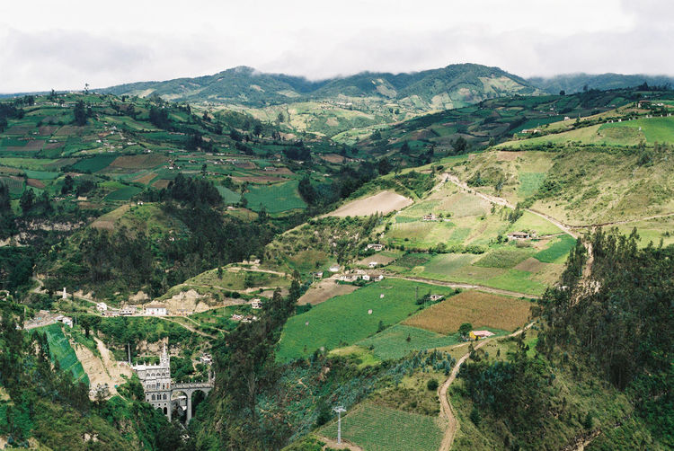 Cathedral in the rolling hills of Colombia Aerial View Agriculture Cathedral Church Colombia Day Faith Field Green Color Landscape Las Lajas Cathedral Mountain Nature No People Outdoors Patchwork Landscape Rolling Hills Rural Scene Scenics Sky Tranquil Scene Tranquility Worship