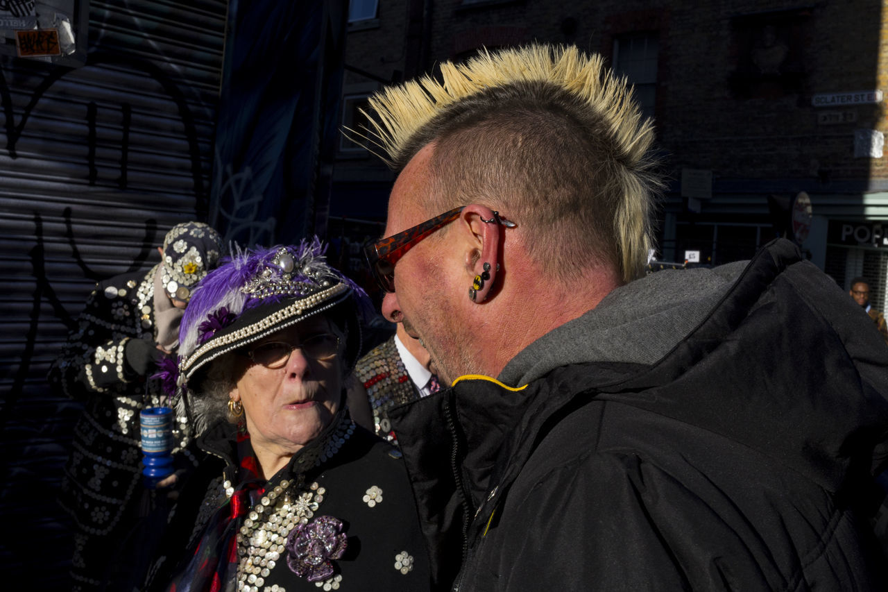 An exchange of views takes place in London's brick lane between a punk and a Pearly Queen, a local of London. Brick Lane Ear Piercing London East End Pearly Queen Adults Only Eastender Eastenders Hat Outdoors Punk Punk Rock Rebel Shock Street Street Photography Streetphotography Sun Sunglasses Two People Uk