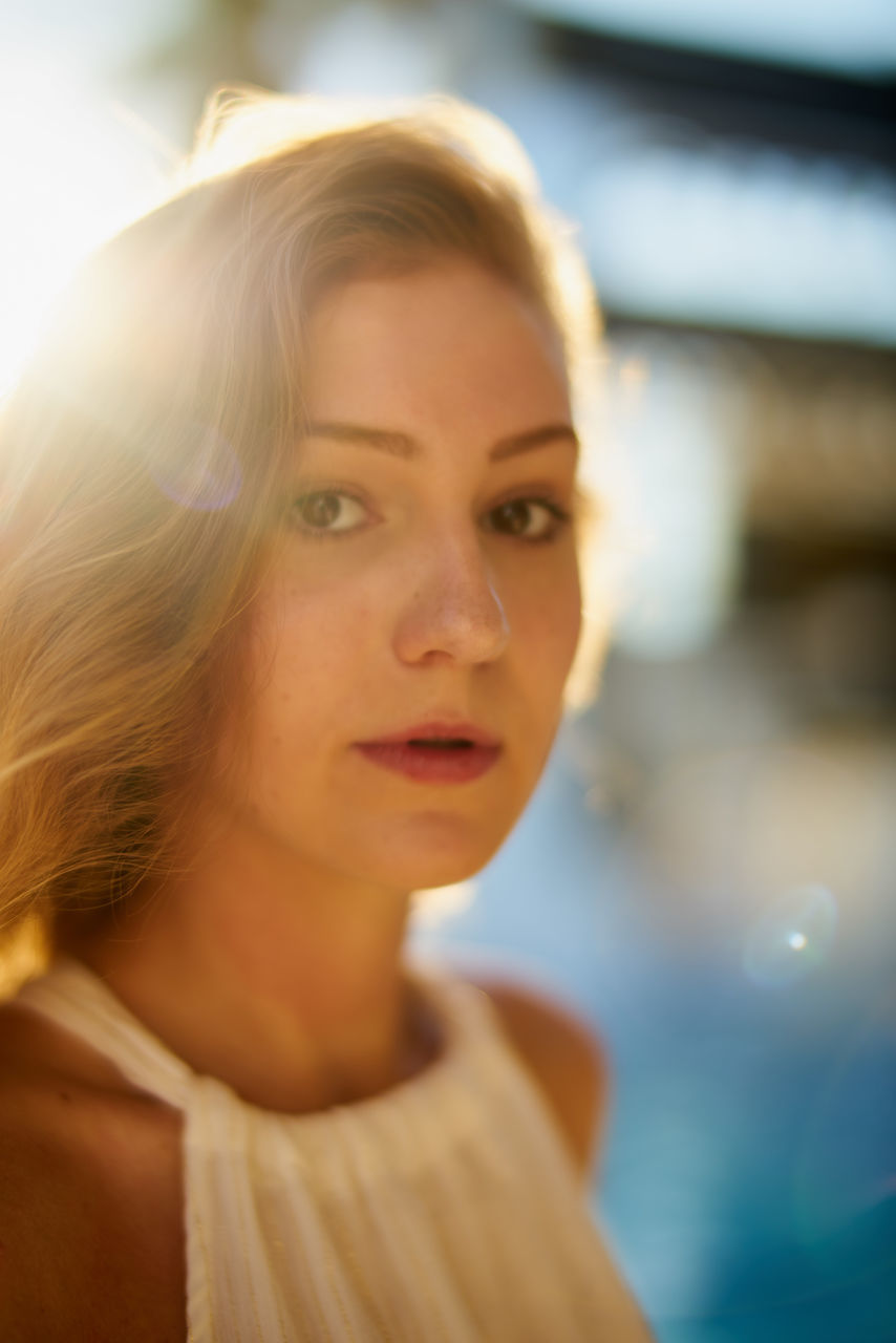 Close-Up Portrait Of Beautiful Young Woman With Blond Hair On Sunny Day