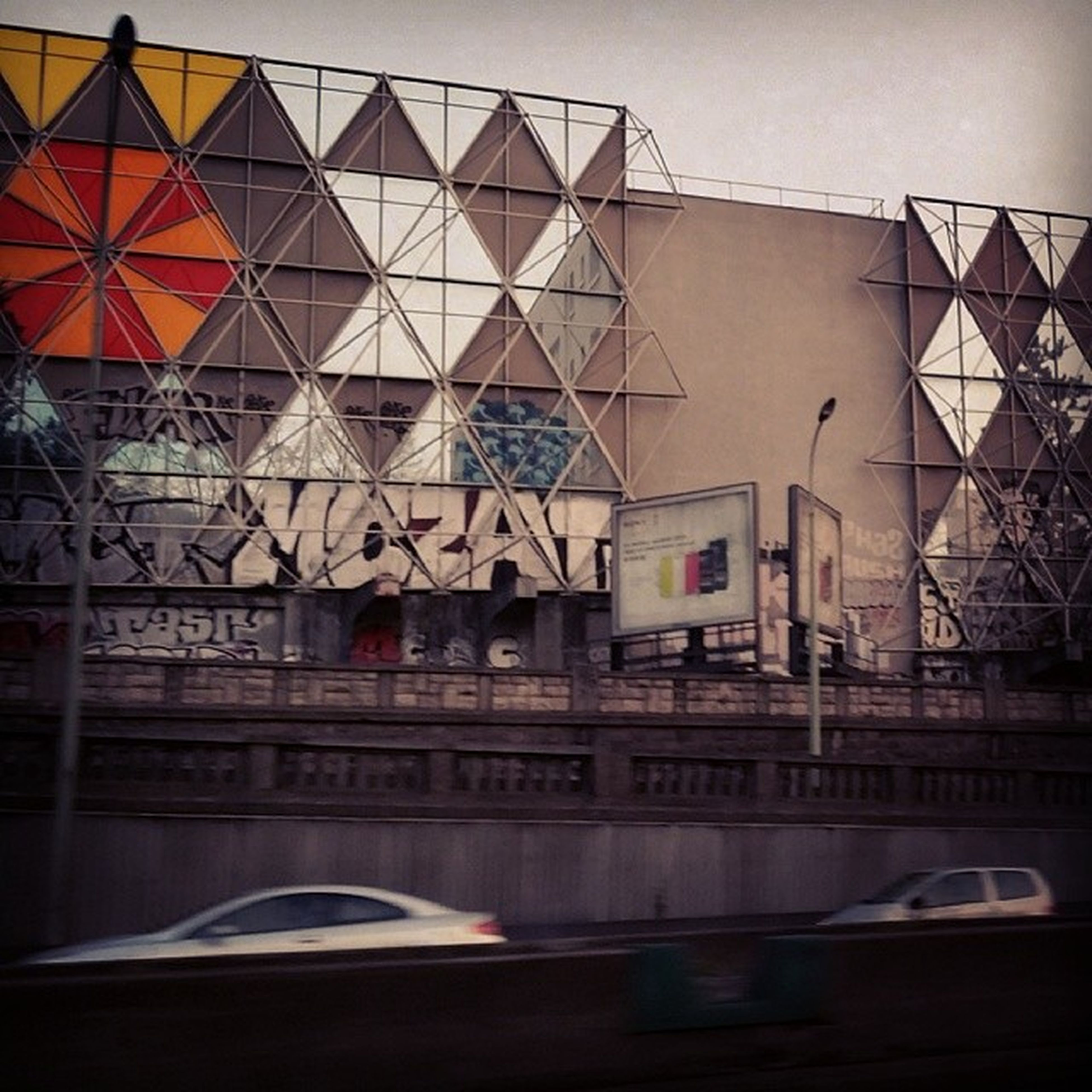architecture, built structure, building exterior, graffiti, low angle view, sky, text, western script, building, communication, outdoors, art, wall - building feature, no people, day, clear sky, metal, window, creativity, city