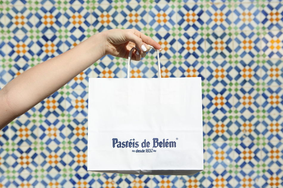 Paper bag with the world famous Pastéis de Belém made from an ancient recipe from the Mosteiro dos Jerónimos. The picture was taken with the original bakery tile background. Bag Bakery Close-up Famous Hand Holding Human Hand Lisbon Paper Pasteis De Belem Pastel Pastel De Belém Pastel De Nata Portugal Portuguese Sweets Tarts Tile Tiles Tourist Attraction  Wall