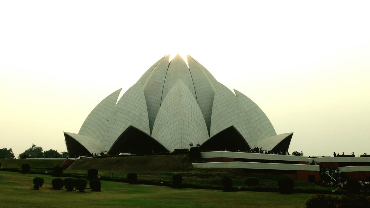 Lotus Temple in New Delhi, India. Travel Destinations Clear Sky Famous Place Lawn Outdoors History Architectural Feature Monument Tranquility Tranquil Scene Vacations Architecture Built Structure Bahai Temple Lotus Temples Clear Sky Pyramid Travel Destinations Field Famous Place Tourism Lawn Outdoors History