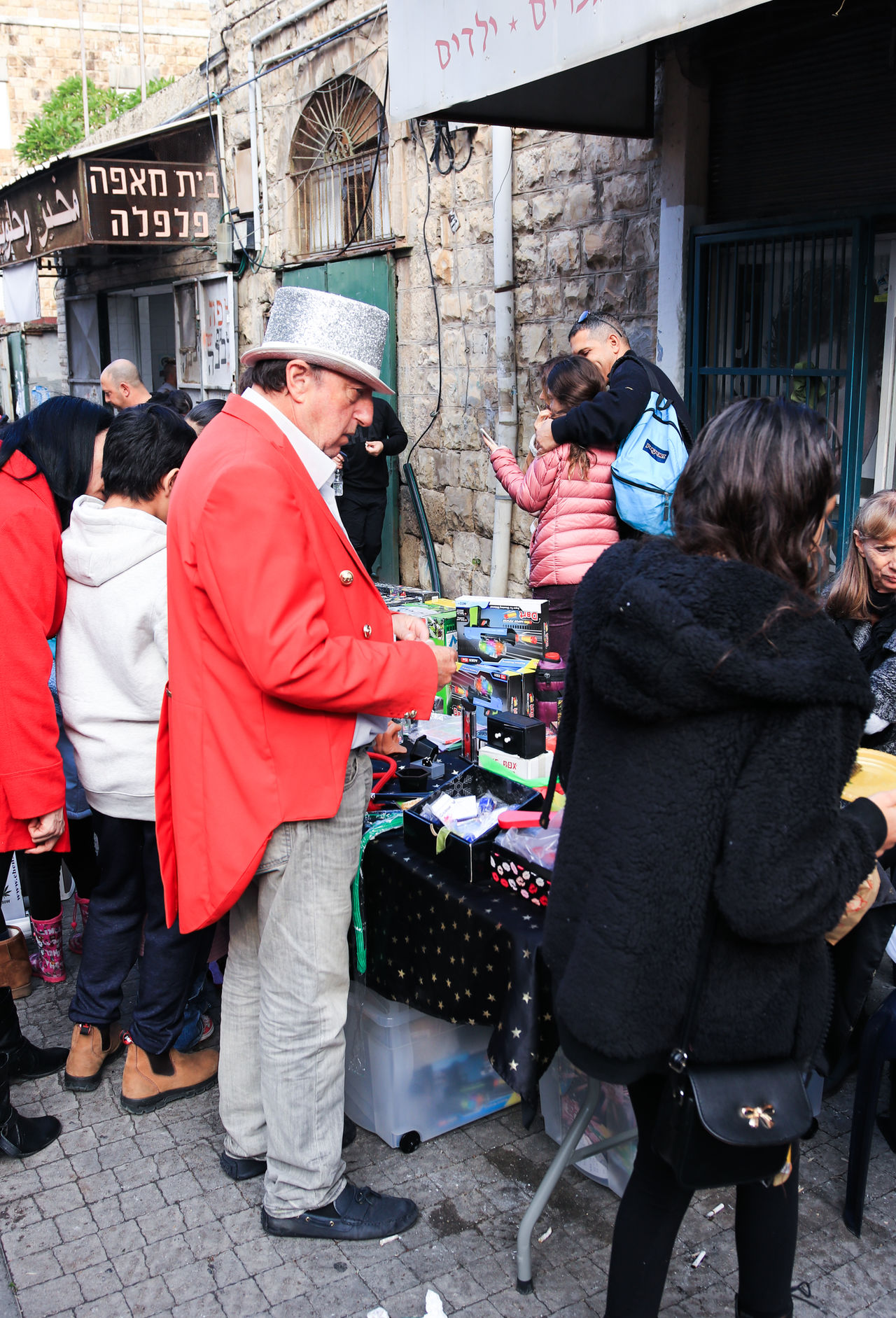 Haifa, Israel - December 17, 2016 : Seller of supplies for focuses is stands at the table with the goods at the Christmas market in the German Colony in Haifa, Israel Business Christmas Colony Day December Focuses German Goods Haifa Happy Holiday Israel Magician Market Men Outdoors People Price Product Salesman Seller Shop Store Supplies Table