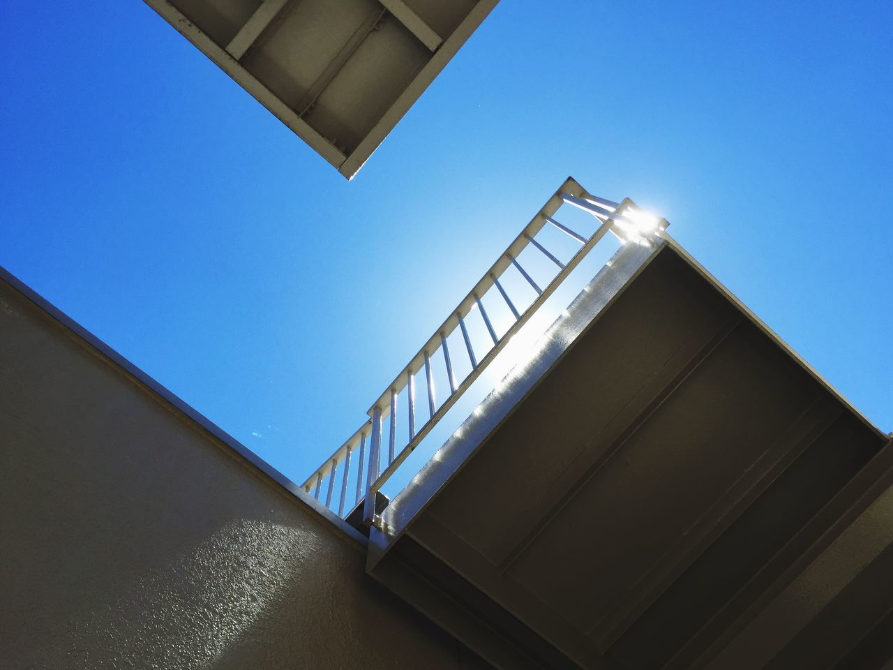 architecture, staircase, low angle view, built structure, steps and staircases, railing, steps, clear sky, day, outdoors, no people, hand rail, sky
