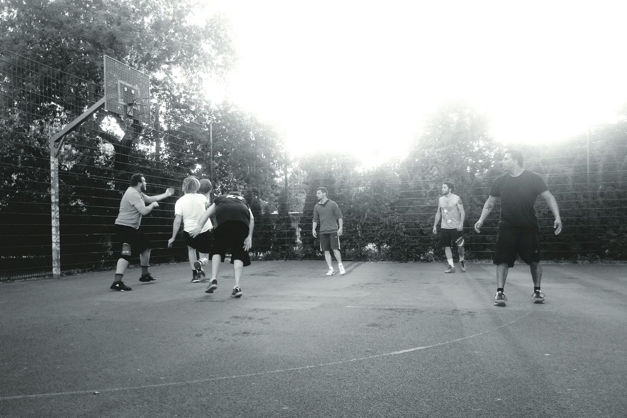 Men Playing Basketball In Court Against Trees
