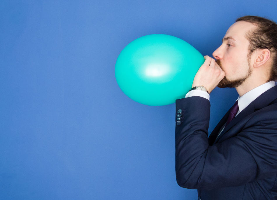 Young handsome bearded man in a suit blowing up a green balloon. Blue background. Balloon Beard Blowing Up Balloon Blue Business Business Finance And Industry Businessman Carefree Confidence  Economy Elegant Flower Helium Balloon Holding Man Manager One Person Party Person Relax Self Portrait Suit Well-dressed Young Adult