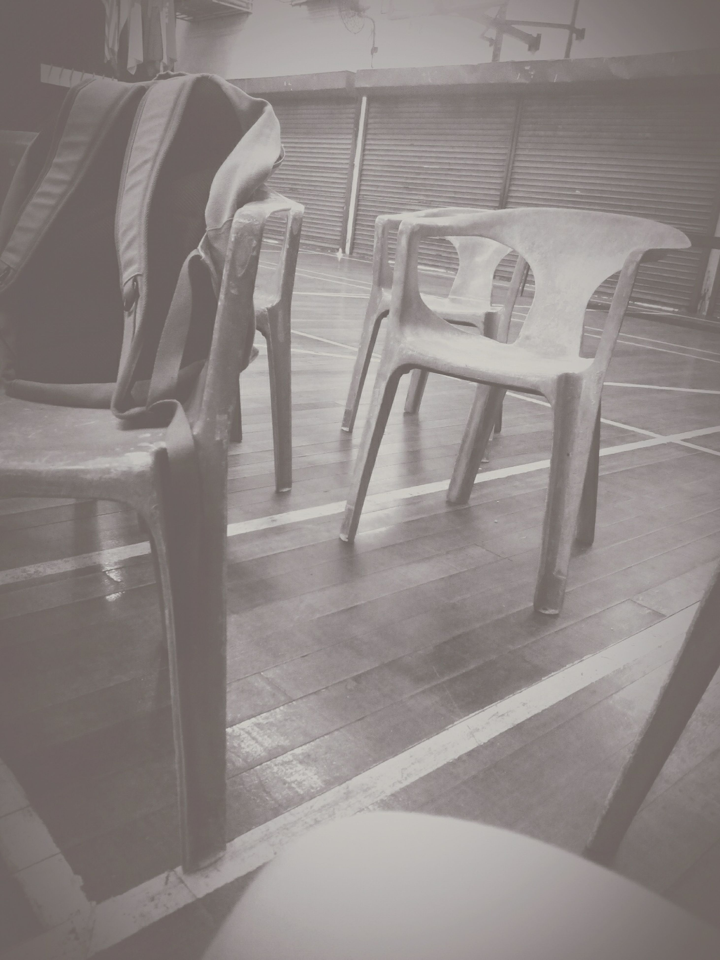indoors, empty, chair, absence, seat, shadow, flooring, sunlight, in a row, tiled floor, table, furniture, no people, day, built structure, high angle view, floor, bench, ceiling, architecture