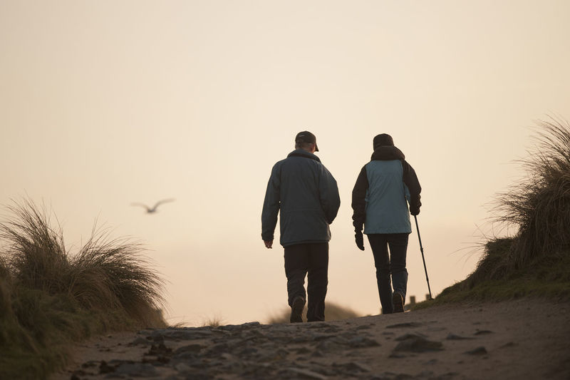 Walking Homeward through the dunes Adult Adults Only Coats Couple Dunes Excercise Fitness Friendship Full Length Grass Hats Lady Man Outdoors Path People Rear View Seagull Stick Sunset Togetherness Two People Walkers Walking Stick