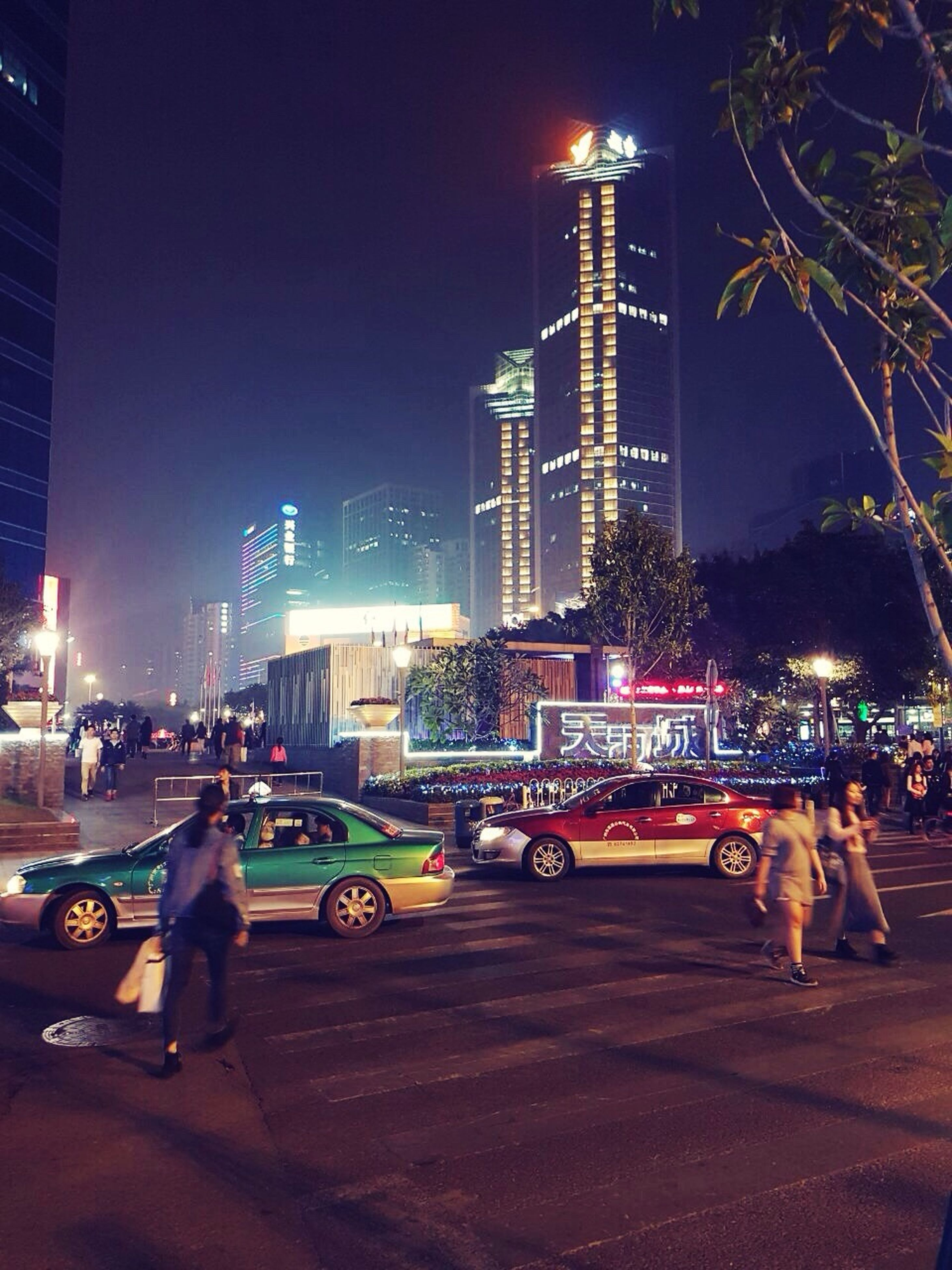 night, illuminated, city, building exterior, travel destinations, architecture, sky, built structure, outdoors, land vehicle, skyscraper, people