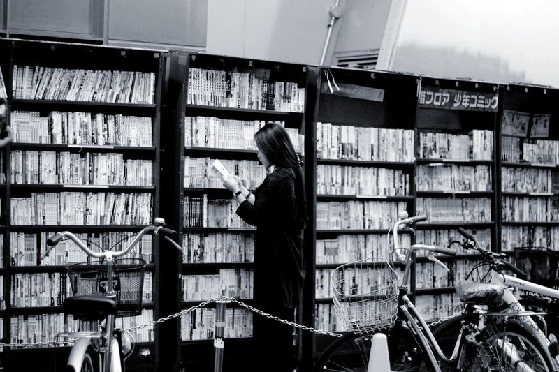 Read carefully. Shelf Bookshelf Library Indoors  Large Group Of Objects Real People One Person Book Standing Day People Adult Streetphotography Street Library Outdoors Reading Read Reading A Book Carefree Freedom OSAKA Japan Photography Cityscape City Photography Black And White Friday