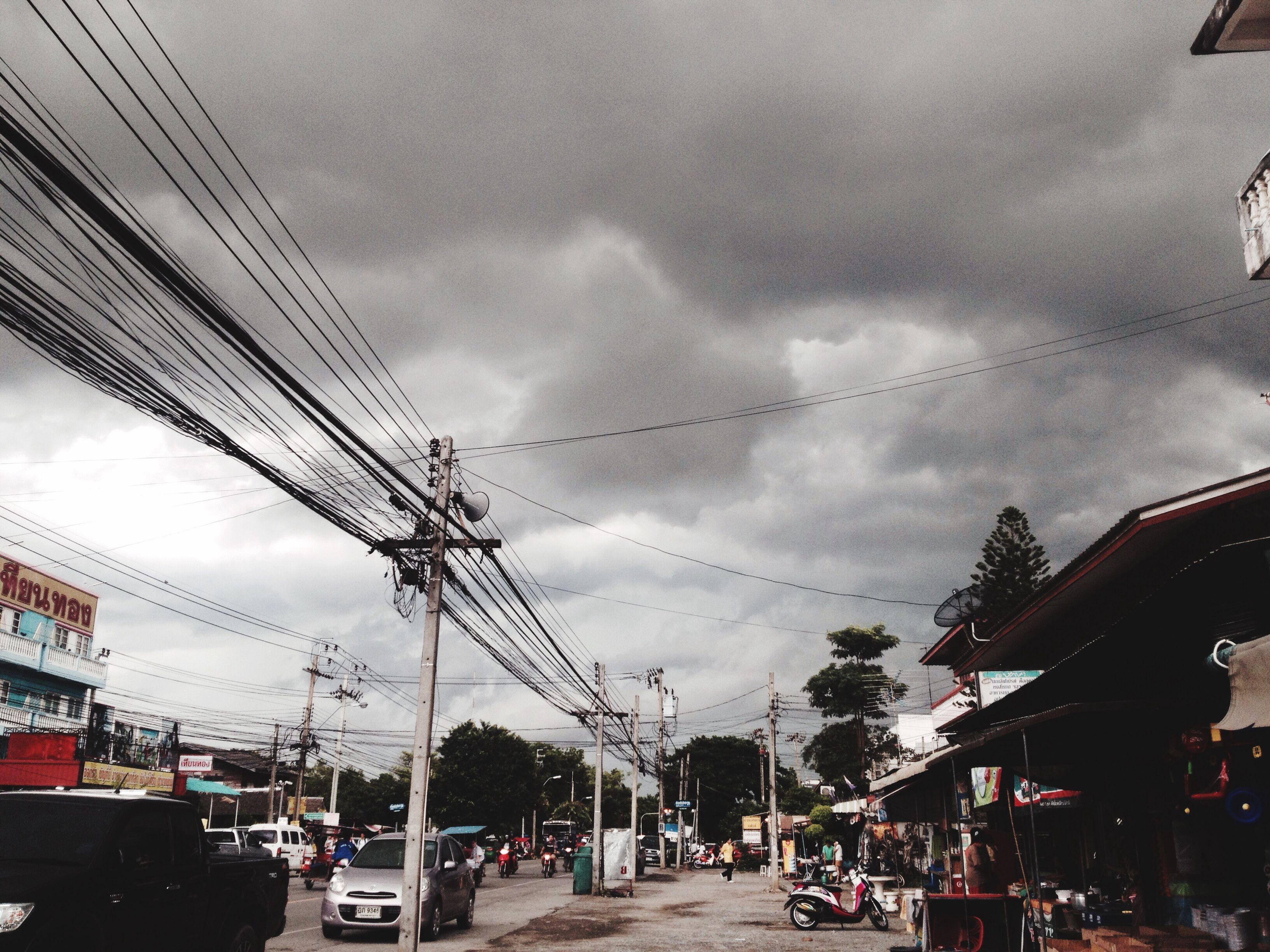 cable, sky, cloud - sky, power line, car, power supply, electricity pylon, transportation, street, incidental people, electricity, road, built structure, land vehicle, outdoors, day, building exterior, mode of transport, architecture, telephone line, tree, city, people