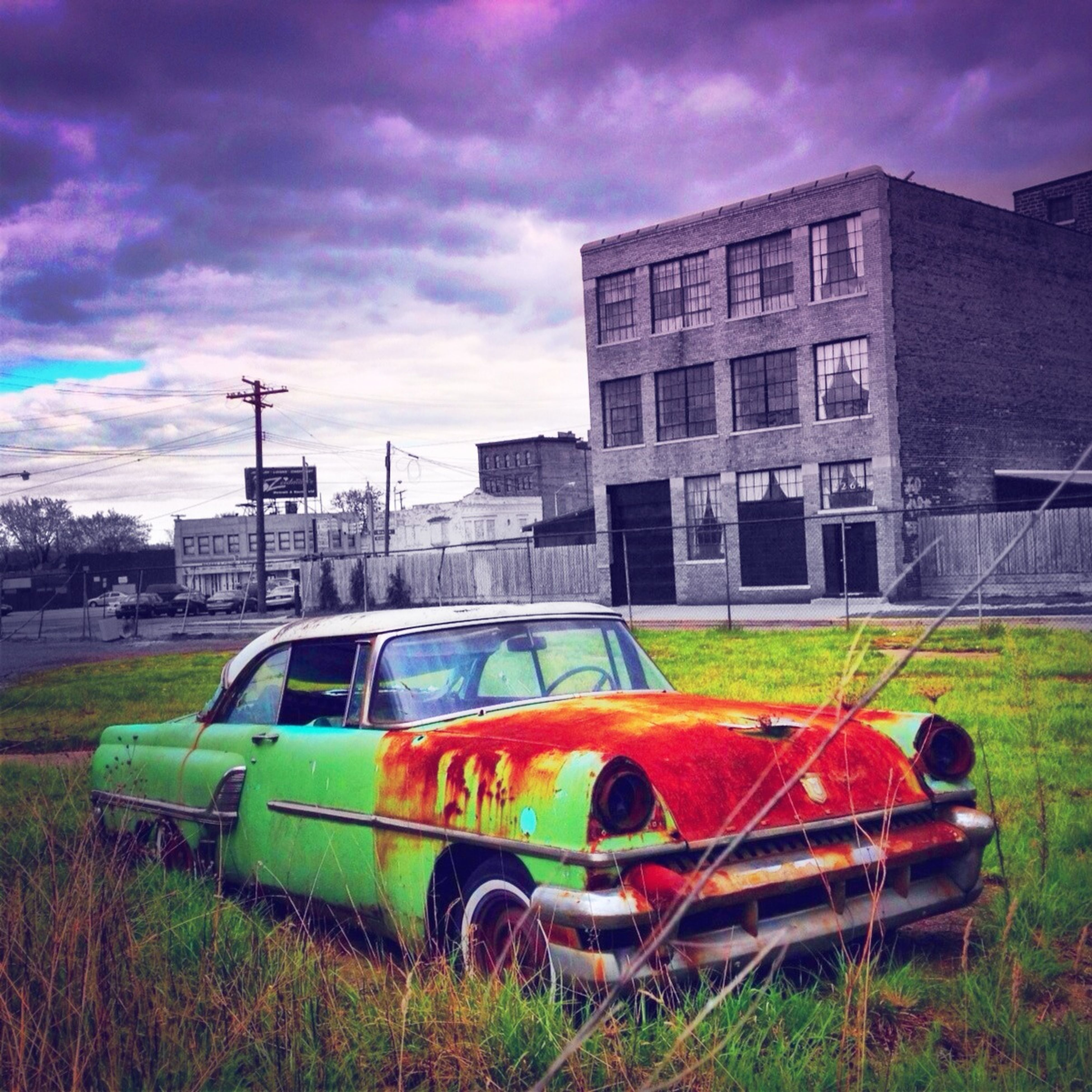 transportation, sky, mode of transport, cloud - sky, land vehicle, architecture, built structure, building exterior, grass, cloud, cloudy, field, abandoned, stationary, car, graffiti, tree, outdoors, day, no people