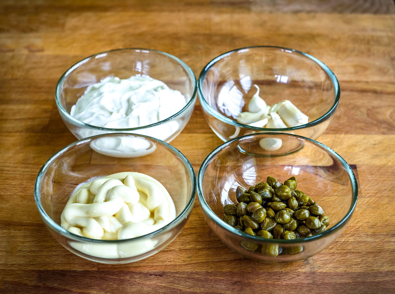 Different ingredients for homemade tartar sauce on wooden desk. Sour creme or creme fraiche, mayonnaise or mayo, capers and garlic in glass bowls. Ready for making of homemade tartar sauce. Homemade Homemade Food Sour Creme Bowl Capers Capri Creme Fraiche Food Food And Drink Freshness Healthy Eating High Angle View Indoors  Mayonnaise No People Preparation  Table Tartar Sauce Wood - Material